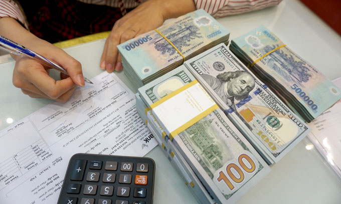 An employee counts U.S. dollar and Vietnamese dong at a bank in Ho Chi Minh City, Vietnam. Photo by VnExpress/Anh Tu